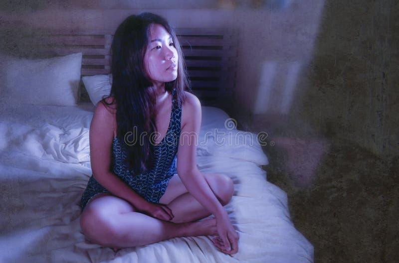 年轻美丽的哀伤和担心的亚裔韩国妇女醒在晚上失眠在看起来的床上周道和沉思遭受的insomn 免版税库存照片