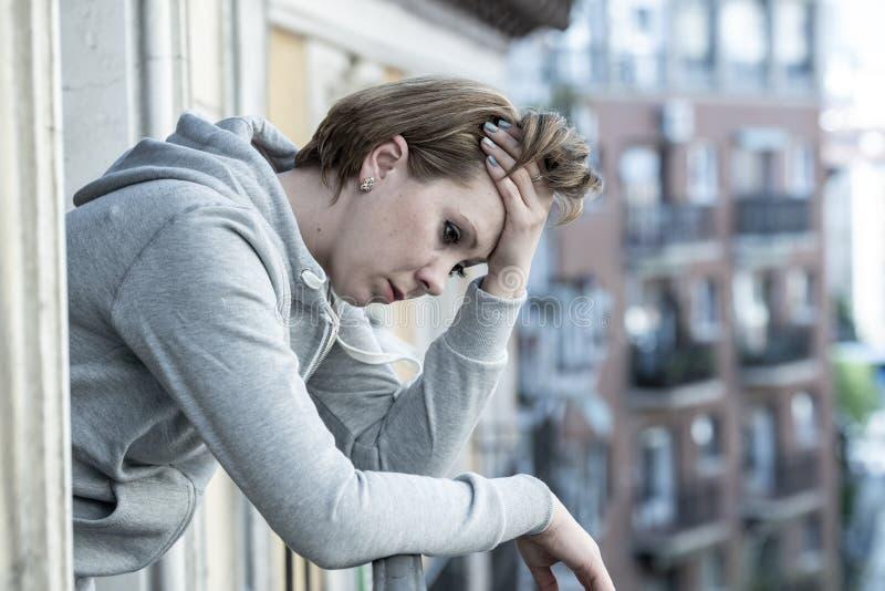 年轻美丽的哀伤的妇女遭受的消沉看在家庭阳台担心有都市看法 库存图片