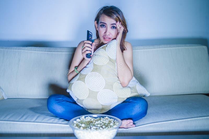 年轻美丽的哀伤的拉丁吃玉米花的妇女观看的戏曲浪漫电影在家坐沙发长沙发夜间在悲伤面孔 免版税库存图片