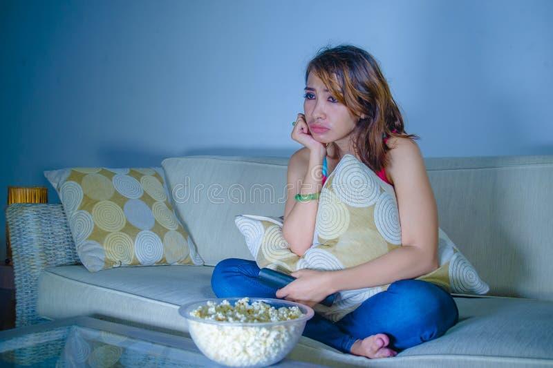 年轻美丽的哀伤的拉丁吃玉米花的妇女观看的戏曲浪漫电影在家坐沙发长沙发夜间在悲伤面孔 免版税图库摄影