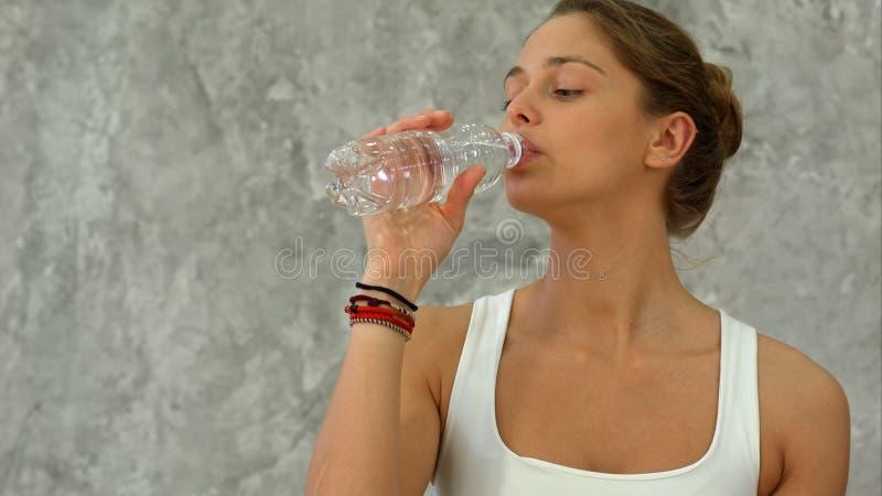 年轻美丽的在瑜伽类以后的妇女饮用水画象  免版税库存图片