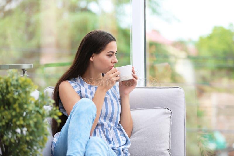 年轻美丽的在窗口附近的妇女饮用的早晨咖啡在家 免版税库存照片