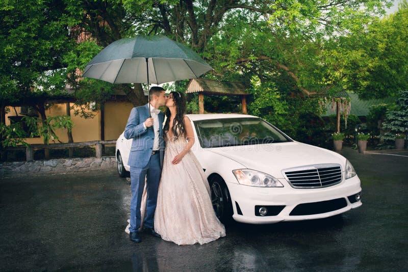 年轻美丽的夫妇新娘和新郎在白色汽车背景有伞的 图库摄影