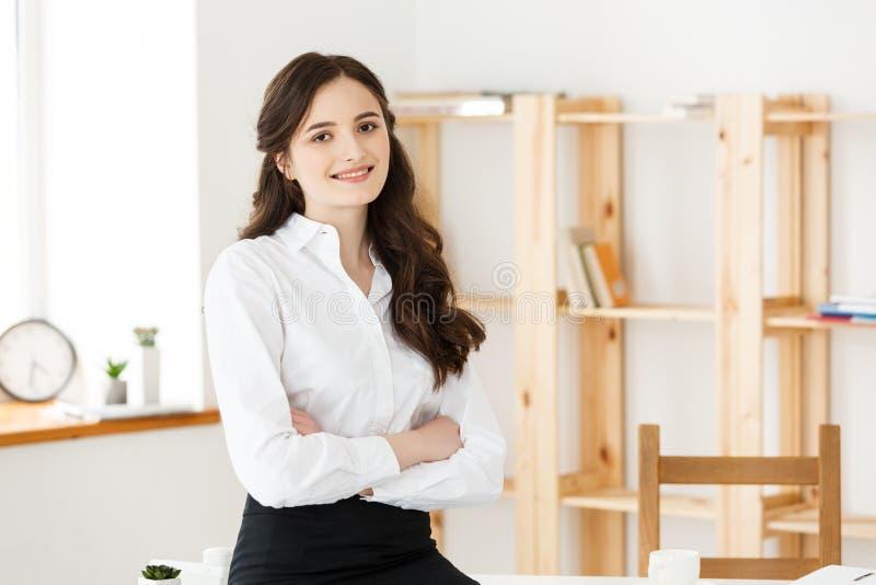 年轻美丽的女商人画象在办公室 Smilling和横渡的胳膊 免版税库存照片