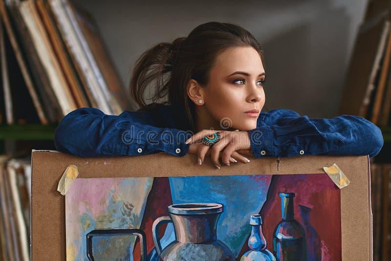 年轻美丽的女孩、女性艺术家拿着一件完成的图片艺术品的画家认为一个新的艺术品想法的或项目 库存照片