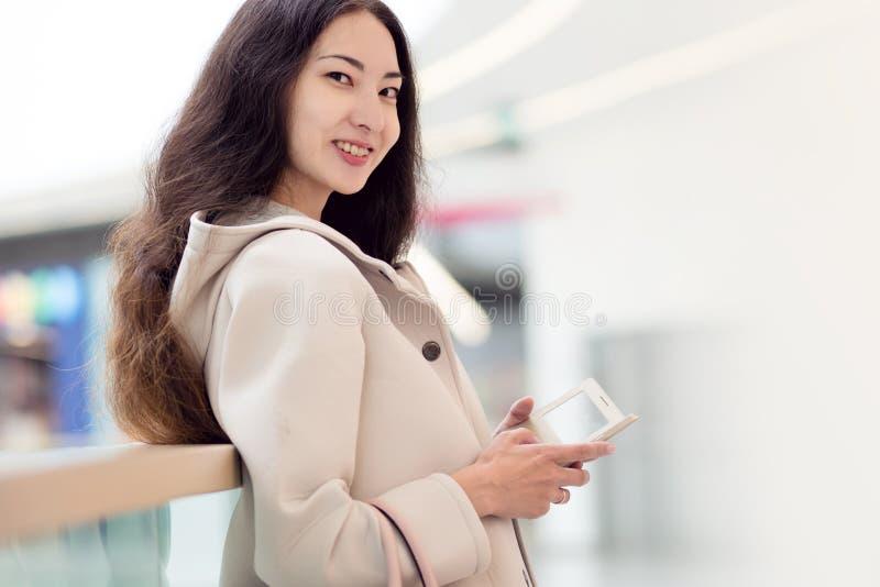 年轻美丽的女孩亚洲人、用途手机,背景、商城或者商业中心 库存图片