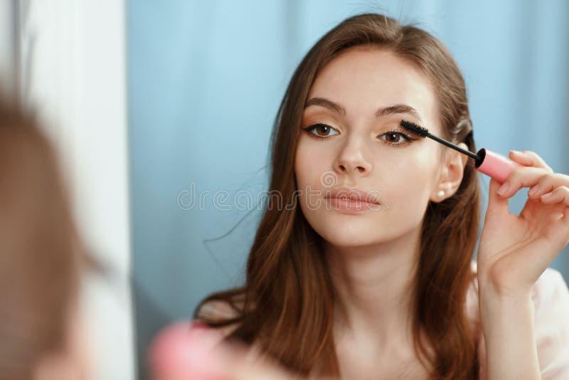 年轻美丽的女孩做自己在镜子前面的构成 免版税库存照片