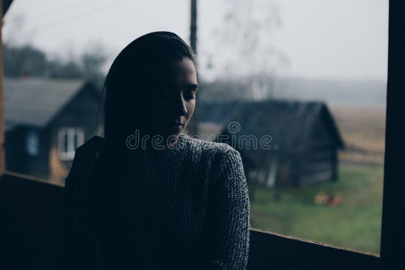 年轻美丽的女孩在村庄 在一个木房子的背景的模型在村庄 黑暗的光 免版税库存图片
