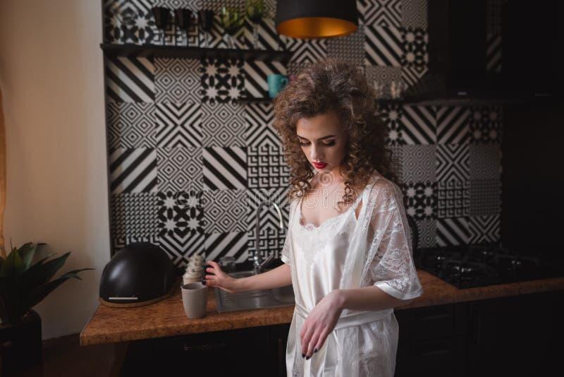 年轻美丽的女孩在火炉附近的厨房在工作台面上把杯子放 库存图片