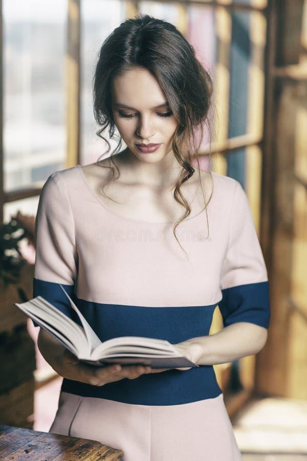 年轻美丽的女孩在窗口附近读书 免版税库存图片