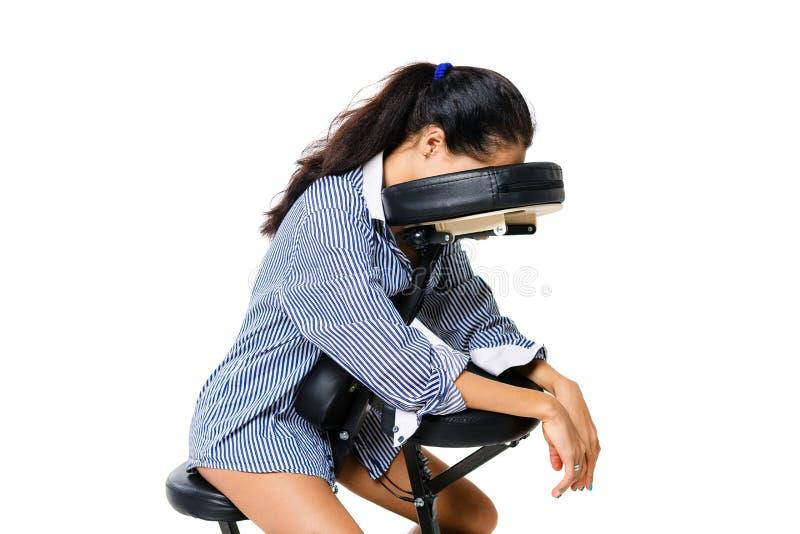 年轻美丽的女孩深色的办公室工作者衬衣的和有光秃的腿的坐按摩椅子 面孔不是可看见的 公共汽车 免版税库存照片