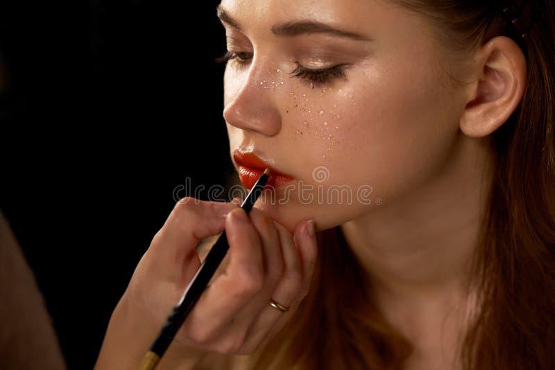 年轻美丽的女孩画象在演播室,有专业构成的 秀丽射击 化妆师绘她的嘴唇与 库存照片