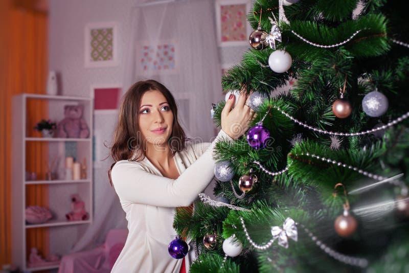 年轻美丽的女孩装饰圣诞树 概念o 图库摄影