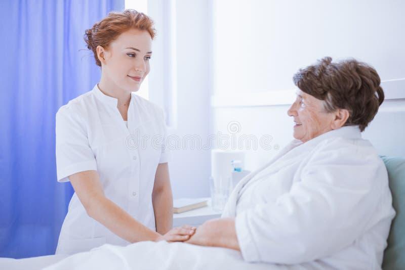 年轻美丽的女性医生和资深患者医院的 免版税库存照片
