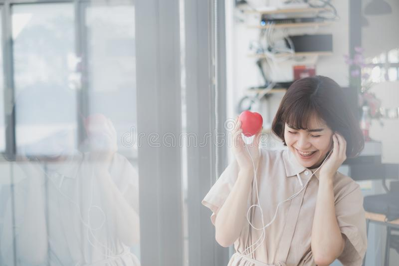 年轻美丽的妇女听从她的心脏的音乐 免版税库存图片