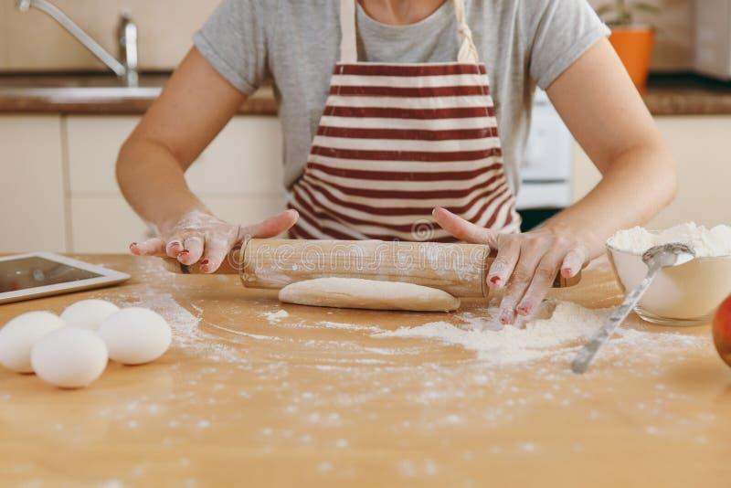 年轻美丽的妇女在厨房里烹调 图库摄影
