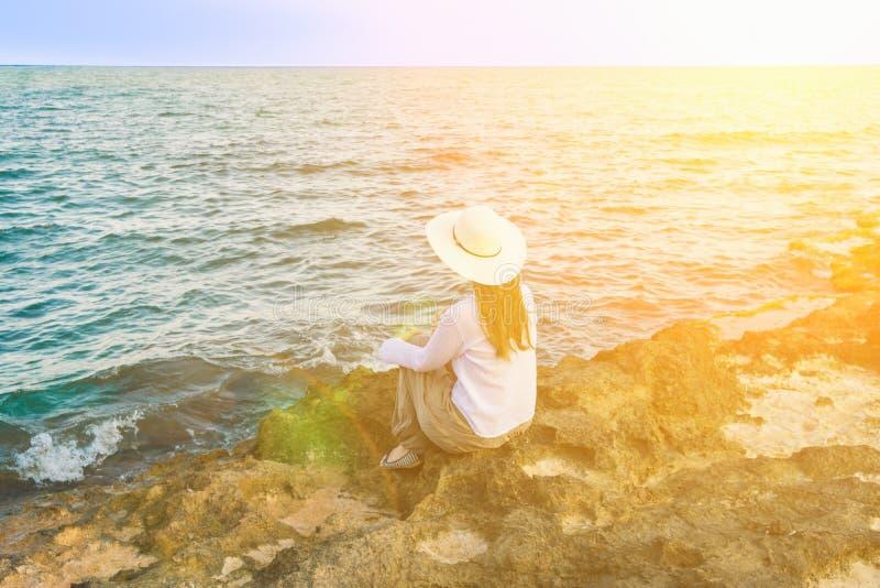 年轻美丽的妇女在Boho给长的头发Sunhat穿衣坐岩石在看绿松石海天线的岸 库存照片