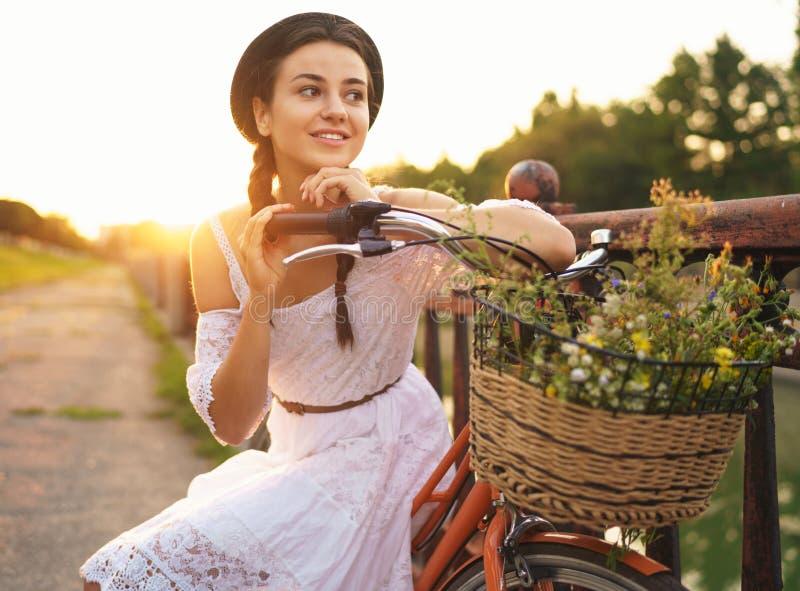 年轻美丽的妇女坐她的有花的自行车在太阳 免版税库存图片