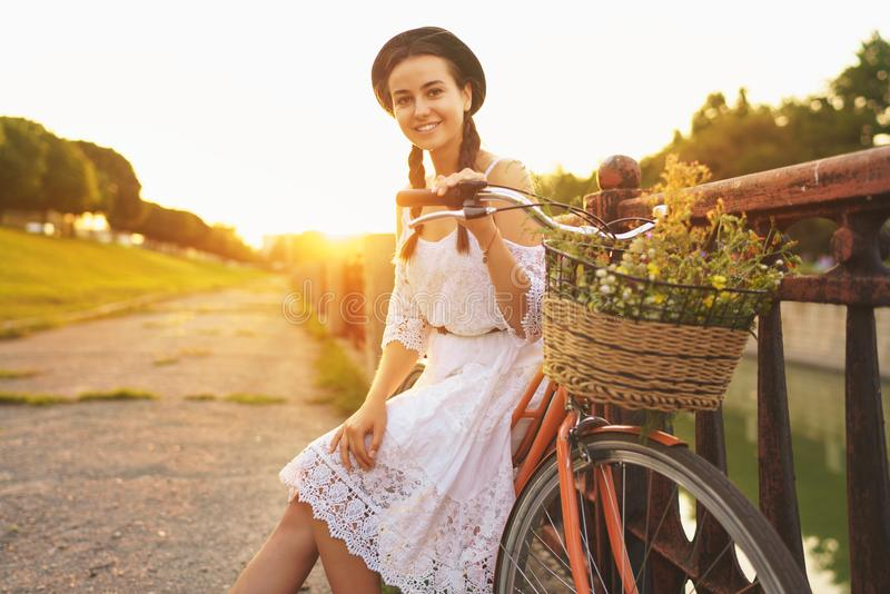 年轻美丽的妇女坐她的有花的自行车在太阳 库存图片
