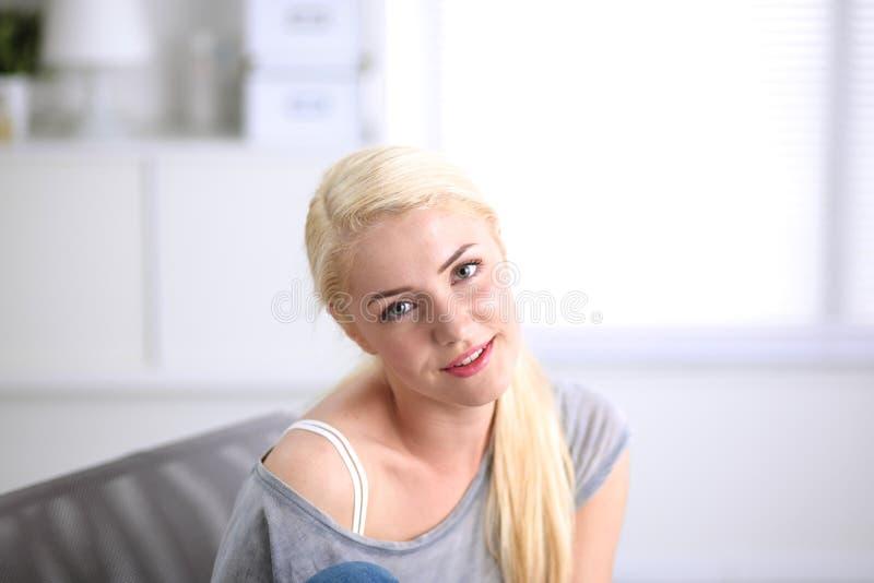 年轻美丽的妇女坐长沙发在她的室 免版税库存照片