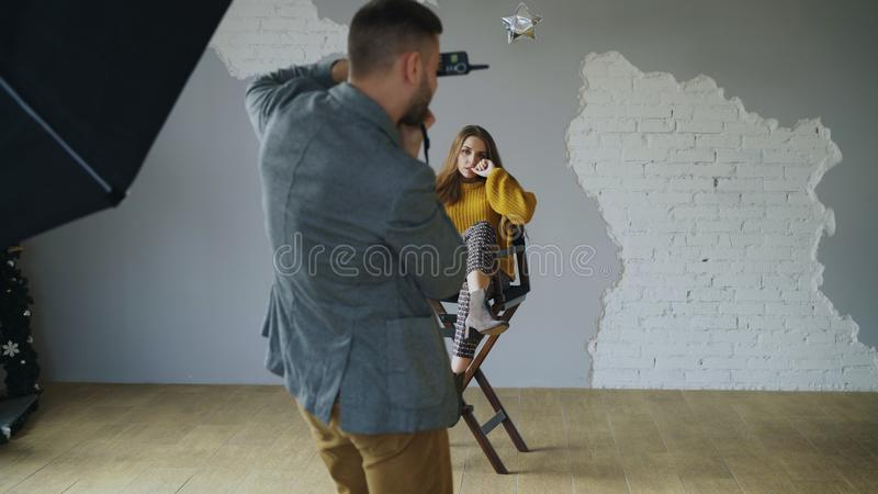 年轻美丽的妇女式样摆在摄影师的,当他射击与一台数字照相机在照片演播室户内时 库存图片