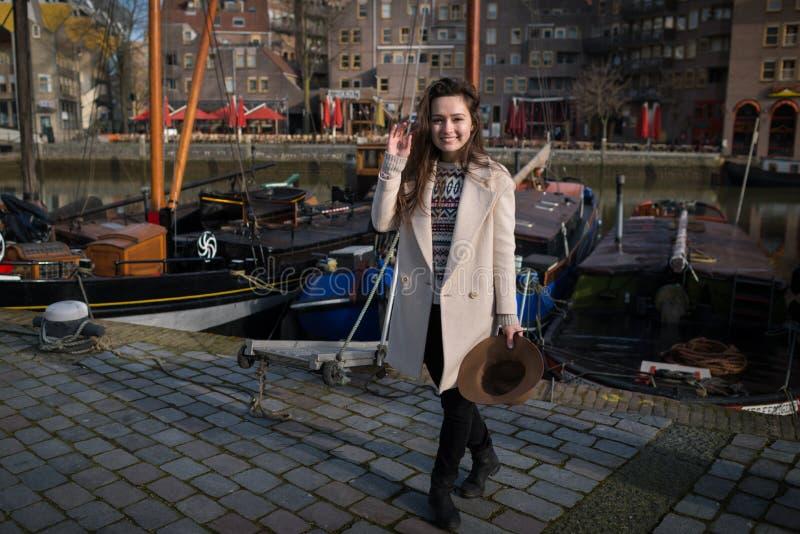年轻美丽的妇女是微笑和站立在老小游艇船坞附近在鹿特丹 免版税库存照片