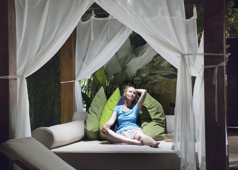 年轻美丽的妇女有休息在大室外床上的温暖的热带晚上在有明亮的颜色枕头的床帷幕下 免版税图库摄影