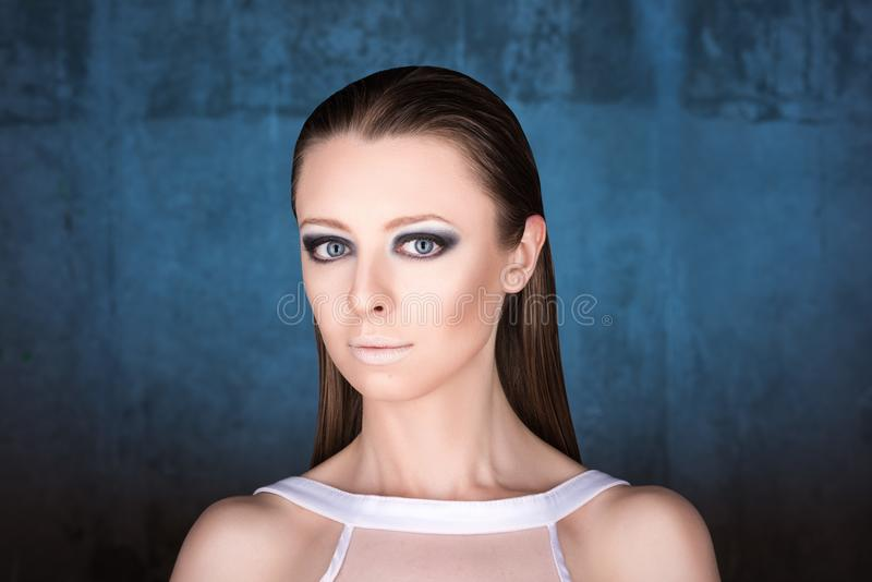 年轻美丽的妇女水平的时尚画象深蓝背景的 湿头发的作用 免版税库存照片