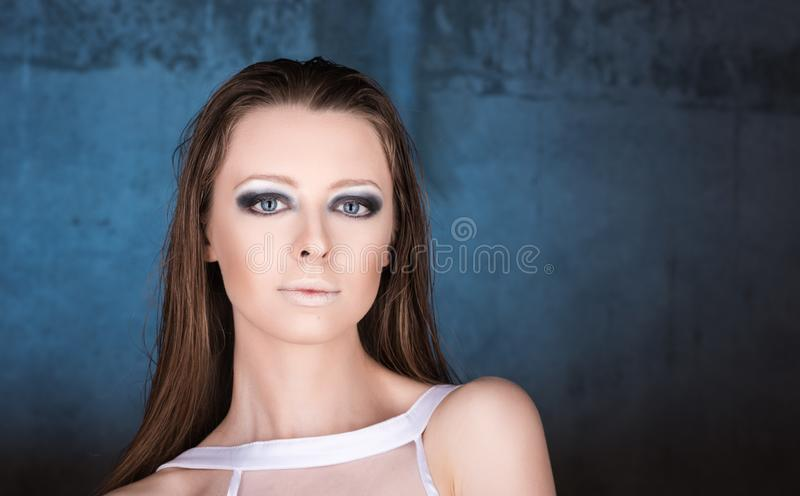 年轻美丽的妇女水平的时尚画象深蓝背景的 免版税库存照片
