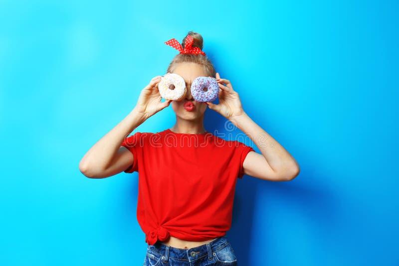 年轻美丽的妇女用在背景的多福饼 免版税图库摄影