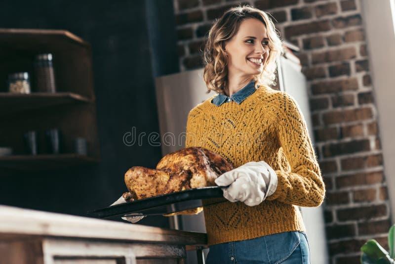 年轻美丽的妇女运载的盘子用可口火鸡 库存图片