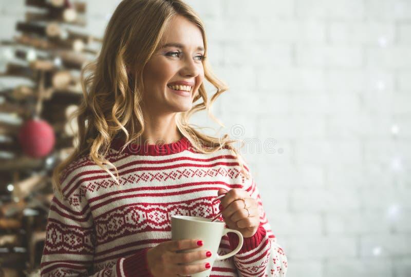 年轻美丽的妇女饮用的咖啡弄脏了冬天雪树背景 库存照片