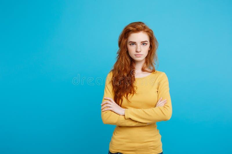 年轻美丽的姜妇女画象有嫩严肃的面孔横穿的武装看照相机 隔绝在柔和的淡色彩 库存照片