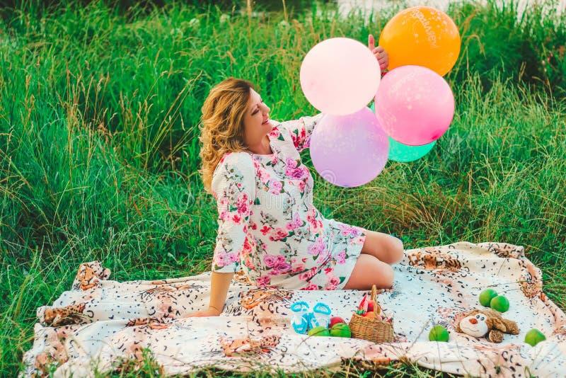 年轻美丽的孕妇在野餐坐一条毯子在有五颜六色的气球的公园在手特写镜头 库存照片