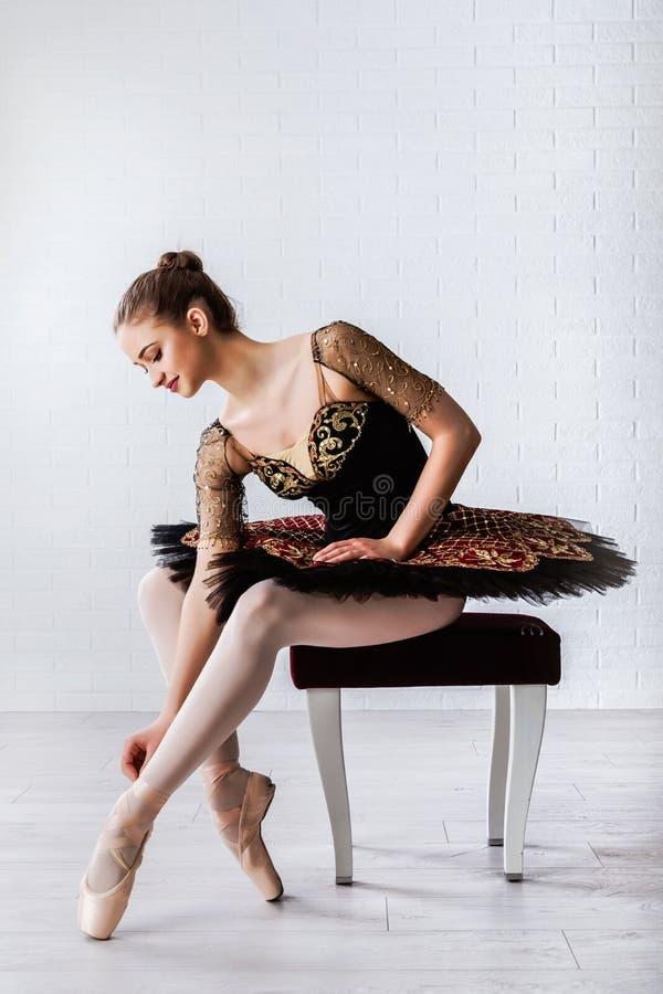 年轻美丽的完善的芭蕾舞女演员画象坐椅子户内 库存图片