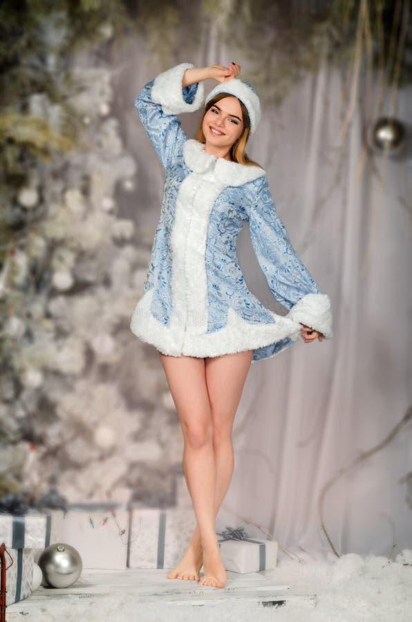 年轻美丽的微笑的女孩画象在冬天多雪的森林,下雪未婚 库存照片