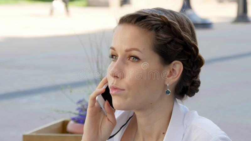 年轻美丽的微笑的妇女谈话在手机 免版税库存照片