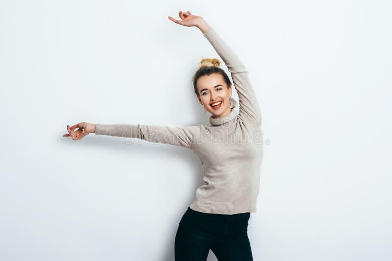 年轻美丽的快乐的妇女用佩带在牛仔裤和毛线衣的头发小圆面包跳舞和摆在白色墙壁 好心情 举起手来 免版税库存图片