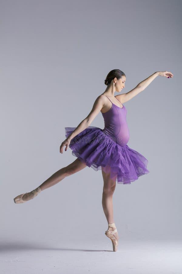 年轻美丽的怀孕的芭蕾舞女演员在演播室摆在 免版税库存图片