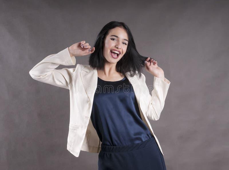 年轻美丽的愉快的女实业家快乐的阳表示支撑深色的演播室 免版税库存图片