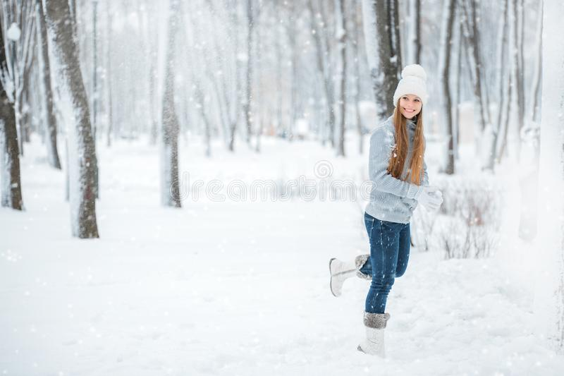 年轻美丽的愉快的微笑的女孩、佩带的时髦的被编织的冬天帽子和手套室外特写镜头画象  跑thr的女孩 免版税库存照片