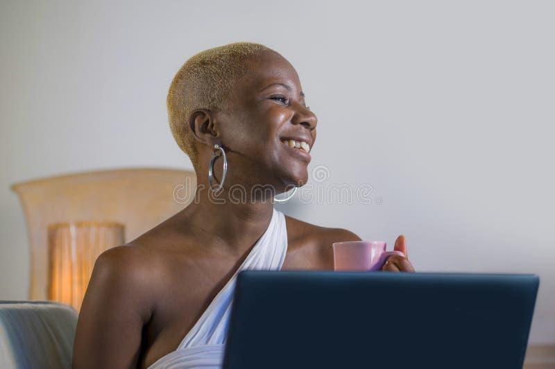 年轻美丽的愉快的黑人美国黑人的妇女微笑的研究便携式计算机在互联网onlin的沙发长沙发在家放松了 免版税库存图片