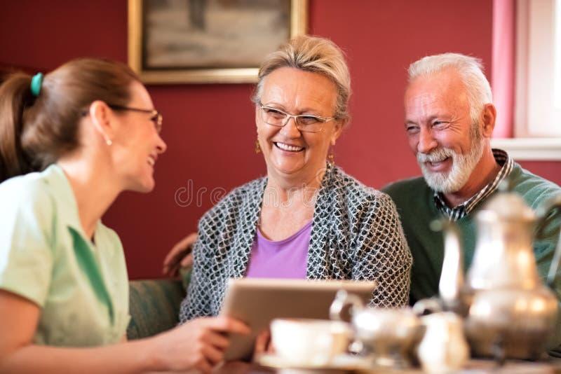 年轻美丽的护士保重关于老人的 库存图片