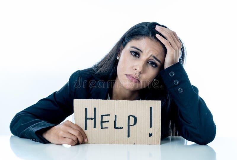年轻美丽的拉丁女商人被淹没和疲倦拿着帮助标志 看注重,不耐烦,沮丧,生气和 免版税库存图片