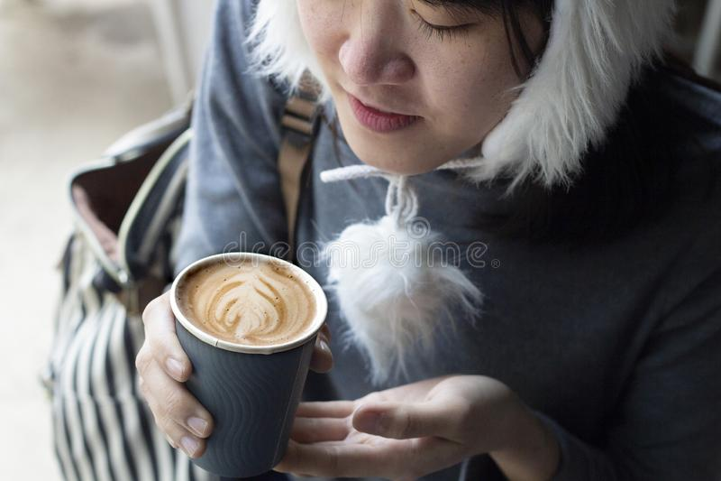 年轻美丽的拿着一个杯子热的咖啡和嗅到它,佩带的冬季衣服的亚洲人愉快的微笑的女孩 免版税库存照片