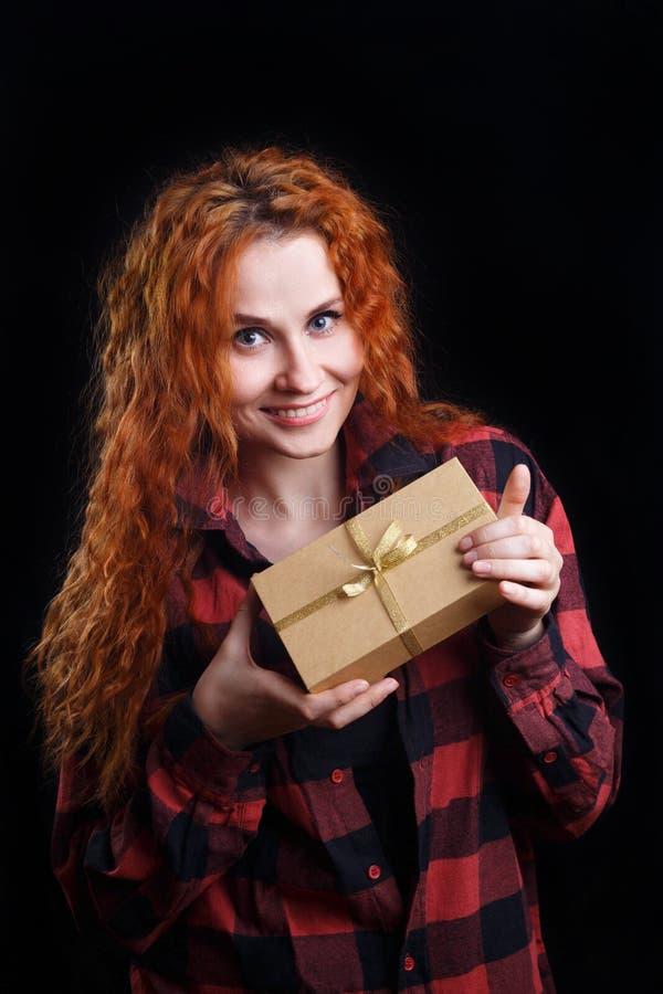 年轻美丽的拿着在黑暗的红头发人微笑的妇女一个礼物盒 库存照片