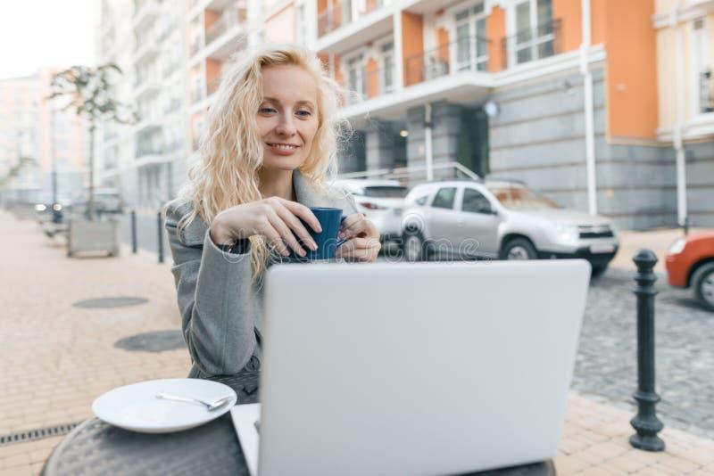 年轻美丽的时兴的白肤金发的妇女画象坐在与手提电脑,水杯的一个室外咖啡馆的衣服暖和的 库存照片