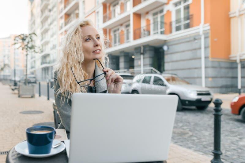 年轻美丽的时兴的白肤金发的妇女画象坐在与手提电脑,水杯的一个室外咖啡馆的衣服暖和的 库存图片