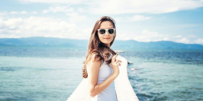 年轻美丽的时髦的太阳镜的白色T恤妇女深色的女孩和在蓝色热带海的岸的牛仔布短裤 免版税库存照片