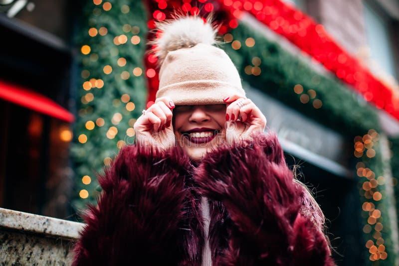 年轻美丽的时髦的女孩无所事事在照相机,拉扯她的在她的前额的帽子并且笑 她佩带人为的伯根地 库存照片